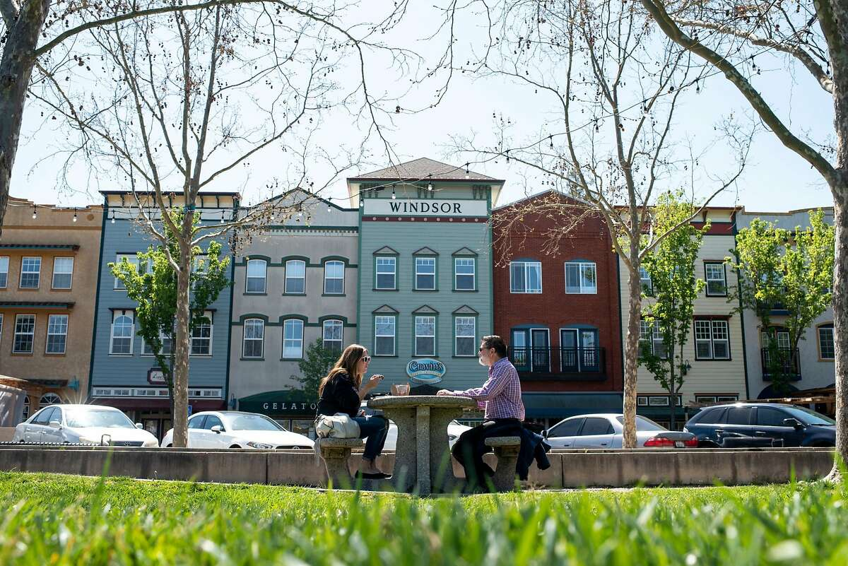 """Jenny Delgado of Windsor, left, and her father, Mario De Bello, eat lunch at the Windsor Town Green on Thursday. """"Whether he's guilty or not, it's going to mess up his political future,"""" De Bello said."""