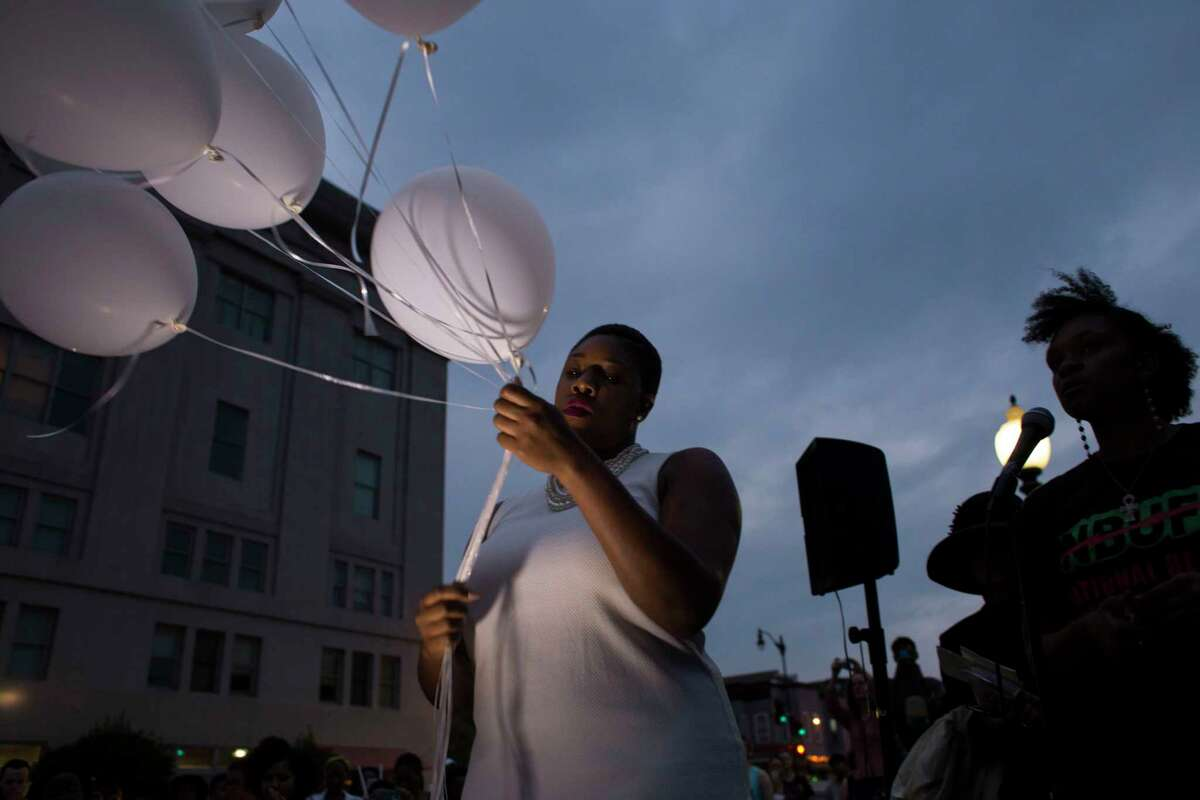 Simon D. Sanders holds balloons before their release as people gather in front of the African-American Civil War Memorial in Washington, D.C., during a June 19, 2015, vigil in remembrance of victims shot and killed June 17 at the historic Emanuel AME Church in Charleston, S.C.