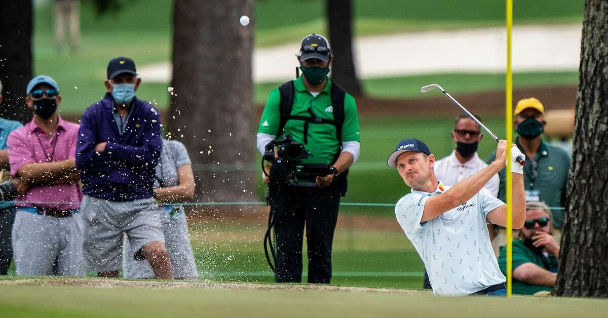 Justin Rose chips out of the bunker on the 15th hole at Augusta National. With a 5-under-par 65, he holds the first-round lead for the fourth time in his Masters career.