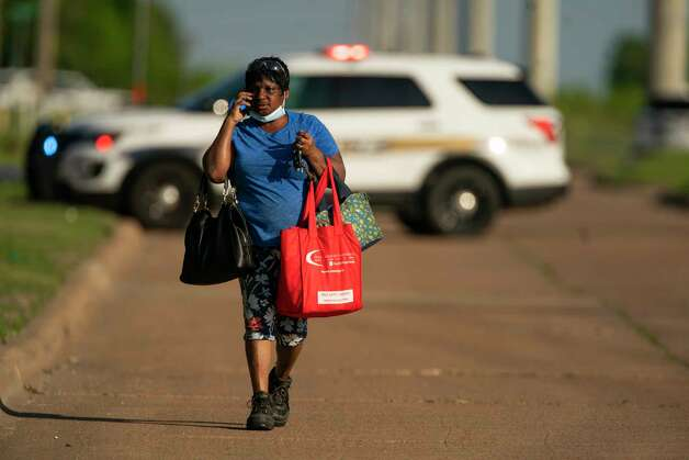 Alice Taylor, who has worked at Kent Moore Cabinets for 26 years, walks away from the scene of a shooting at the business, Thursday, April 8, 2021, in Bryan. At least one person is reported dead, and six people were hospitalized. Taylor described thinking the shooting was cabinets falling off the line, but then realized that an employee was shooting. Photo: Mark Mulligan, Staff Photographer / © 2021 Mark Mulligan / Houston Chronicle