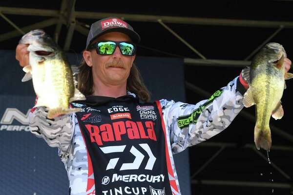 Seth Feider displays his catch at weigh-in on opening day of the Bassmasters Elite fishing tournament and festival in Orange Thursday. The event, which includes a carnival, live music nightly, food and vendors, continues through Sunday. Photo made Thursday, April 8, 2021 Kim Brent/The Enterprise