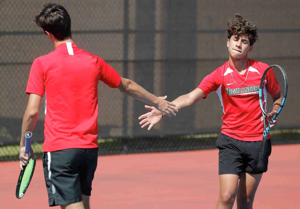 Emilio Lopez of The Woodlands, right, gives a high-five to his doubles partner, Jose Perez after a point in a boys double championship match during the District 13-6A high school tennis tournament at The Woodlands High School, Thursday, April 8, 2021, in The Woodlands.