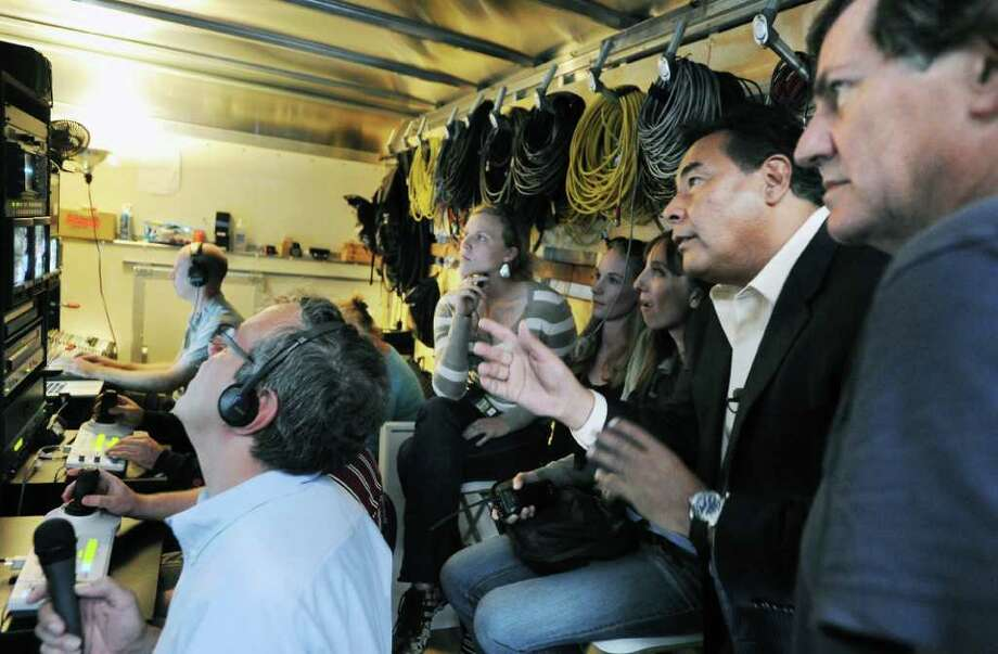 "FILE — John Quinones, anchor of ""What Would You Do?"", discusses a scene in the production trailer with (far right) executive producer Chris Whipple, originally from Old Greenwich, on Forrest St. in Stamford, Conn. on Friday September 10, 2010 Photo: Kathleen O'Rourke / Stamford Advocate"