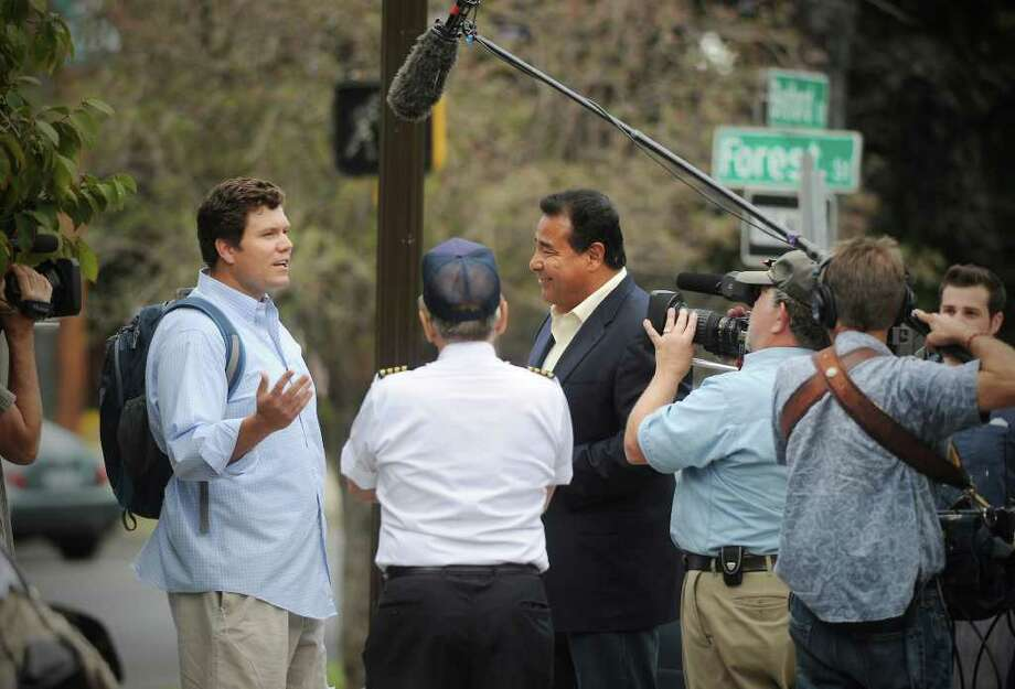"""Aaron Armstrong, of Stamford, is greeted by John Quinones, anchor of """"What Would You Do?"""" as they film a segment at the corner of Bedford St. and Forrest St. in Stamford, Conn. on Friday September 10, 2010 Photo: Kathleen O'Rourke / Stamford Advocate"""