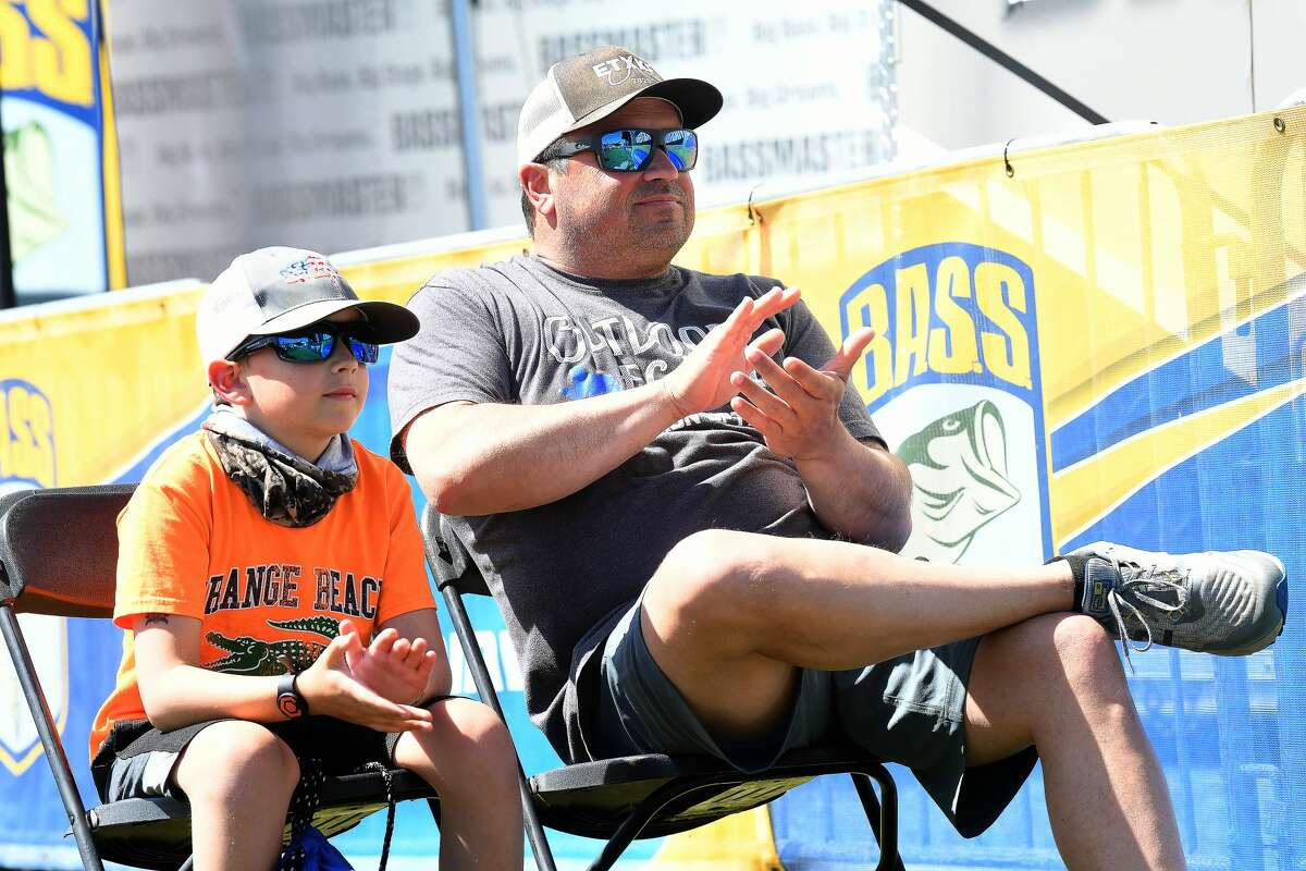 Blake and dad Andrew Middlebrook take in the first weigh-in presentation on opening day of the Bassmasters Elite fishing tournament and festival in Orange Thursday. The event, which includes a carnival, live music nightly, food and vendors, continues through Sunday. Photo made Thursday, April 8, 2021 Kim Brent/The Enterprise