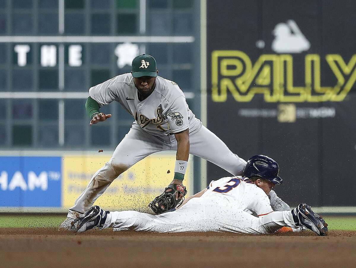Houston Astros Myles Straw (3) steals second base from Oakland Athletics shortstop Elvis Andrus (17) during the fifth inning of the Astros home opener MLB baseball game at Minute Maid Park, in Houston, Thursday, April 8, 2021.