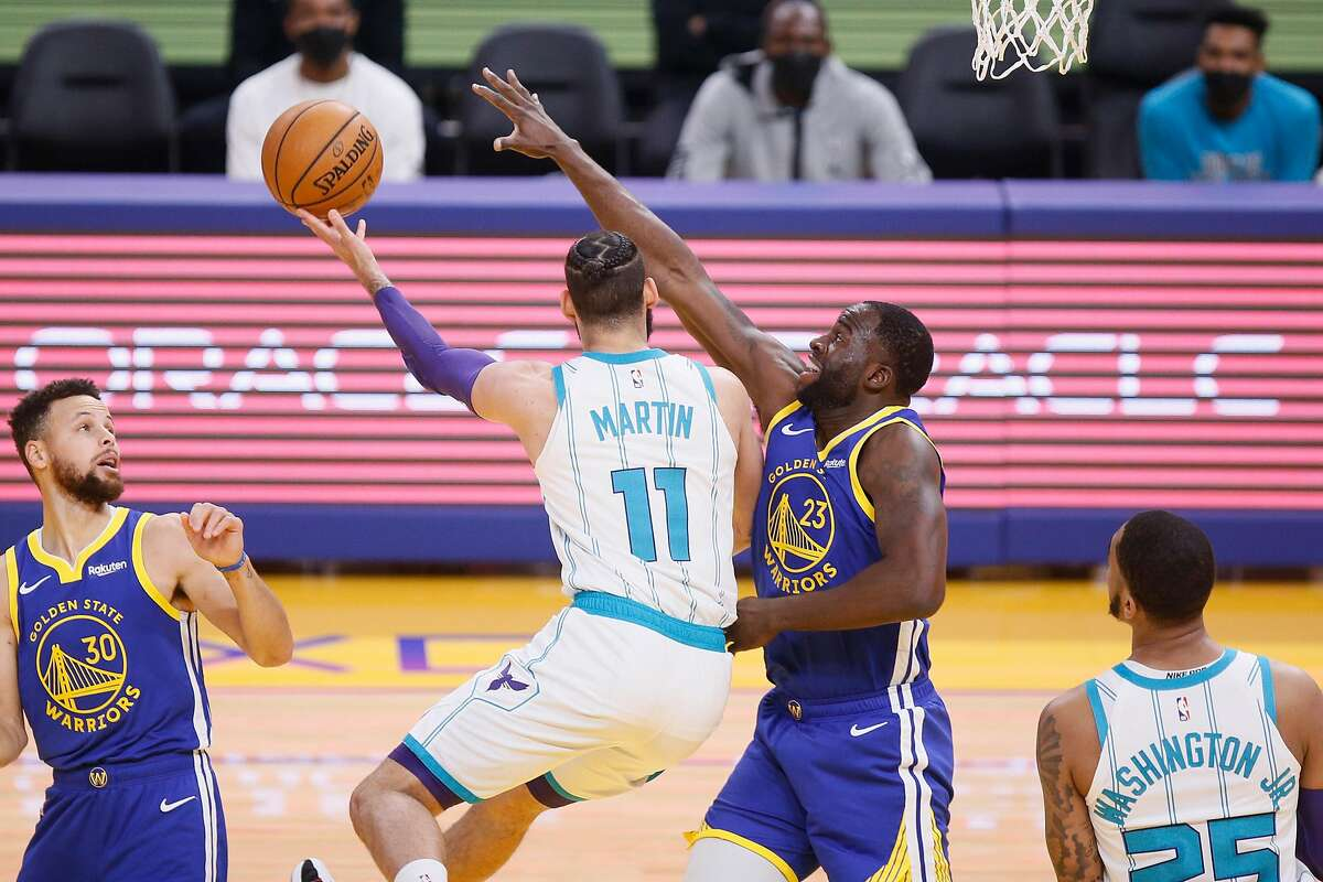 Golden State Warriors forward Draymond Green (23) defends Charlotte Hornets forward Cody Martin (11) in the first quarter of a Feb. 26 game at Chase Center.