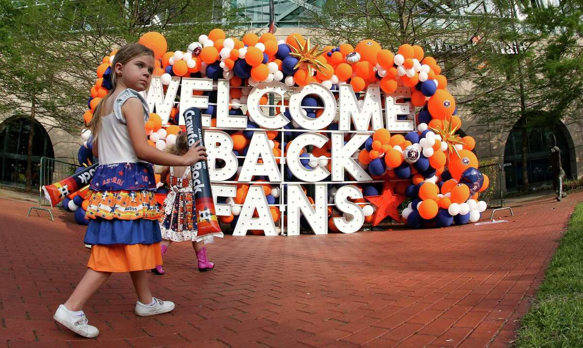 Astro fans pose for photos outside of Minute Maid Park as they make their way tto watch Houston Astros home opener against the Oakland A's in Houston on Thursday, April 8, 2021.