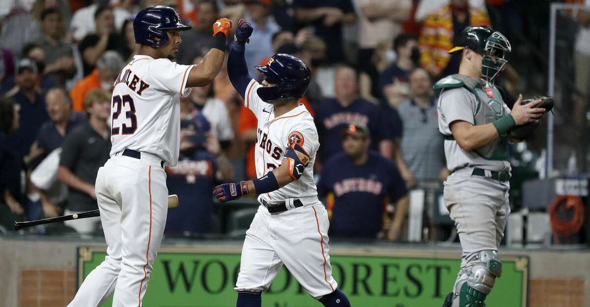 Houston Astros Jose Altuve (27) celebrates with Michael Brantley (23) after hitting a home run during the seventh inning of the Astros home opener MLB baseball game at Minute Maid Park, in Houston, Thursday, April 8, 2021.
