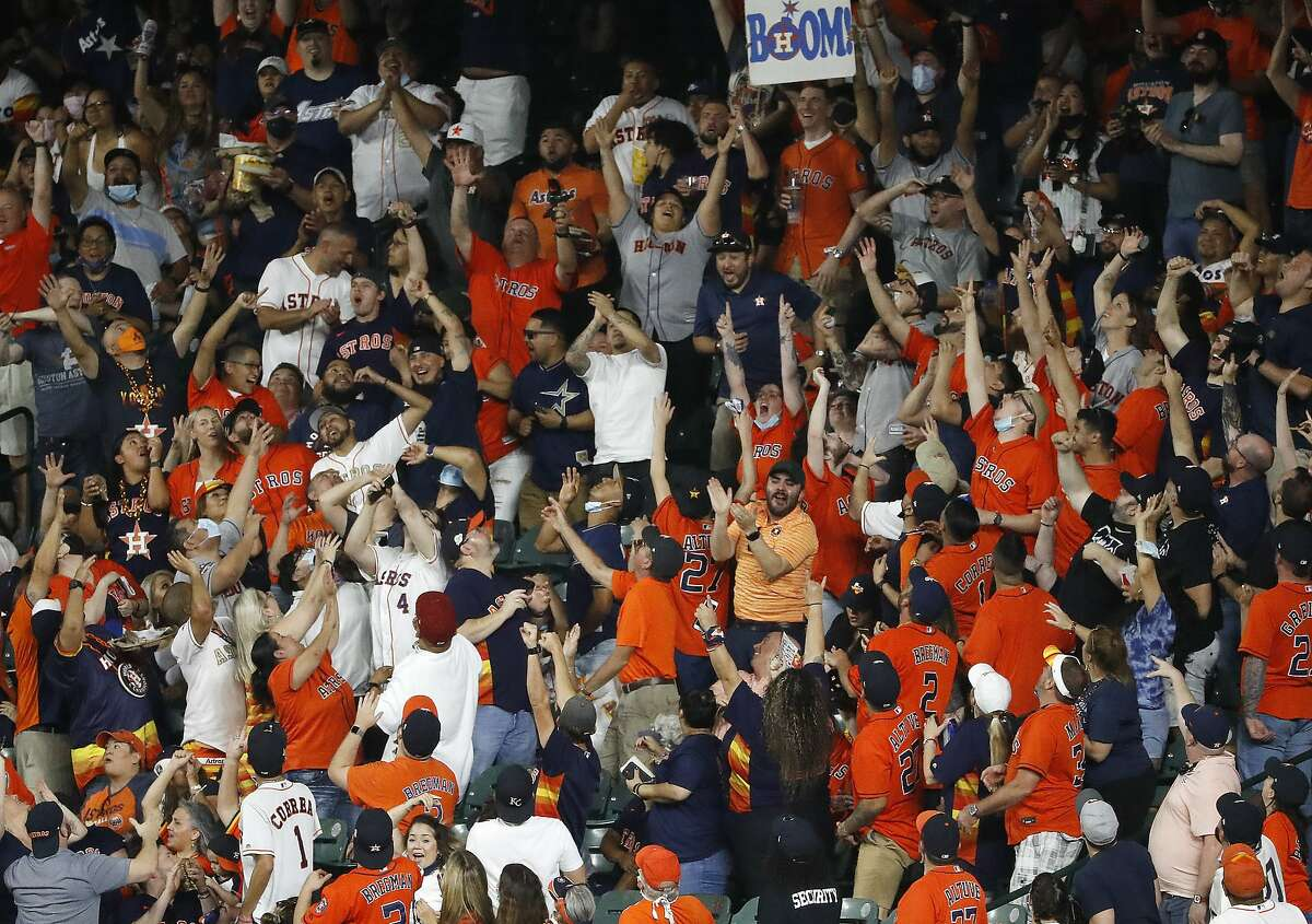 Fans in right field reach for a home run hit by Houston Astros' Yordan Alvarez in the sixth inning against the Oakland Athletics in a baseball game Thursday, April 8, 2021, in Houston. (Kevin M. Cox/The Galveston County Daily News via AP)