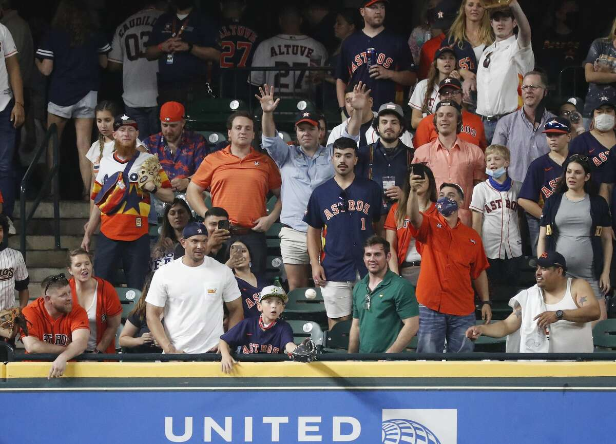 A little boy catches a ball from Houston Astros left fielder Michael Brantley (23) before the start of the ninth inning of the Astros home opener MLB baseball game at Minute Maid Park, in Houston, Thursday, April 8, 2021. Astros beat the Oakland Athletics 6-2.