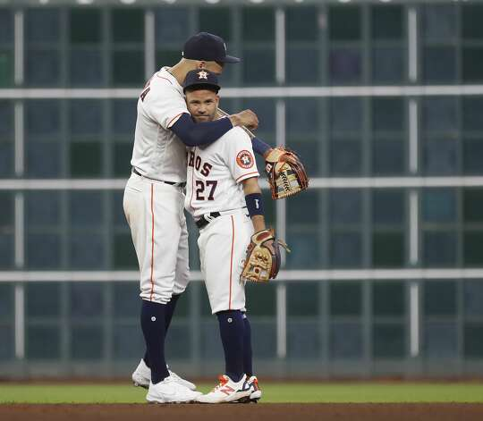 Houston Astros second baseman Jose Altuve (27) hugs shortstop Carlos Correa (1) after the Astros 6-2 win over the Oakland Athletics in the Astros home opener MLB baseball game at Minute Maid Park, in Houston, Thursday, April 8, 2021. Photo: Karen Warren/Staff Photographer / @2021 Houston Chronicle