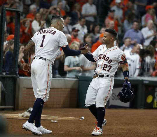 Houston Astros Jose Altuve (27) celebrates with Carlos Correa (1) after hitting a home run during the seventh inning of the Astros home opener MLB baseball game at Minute Maid Park, in Houston, Thursday, April 8, 2021. Photo: Karen Warren/Staff Photographer / @2021 Houston Chronicle