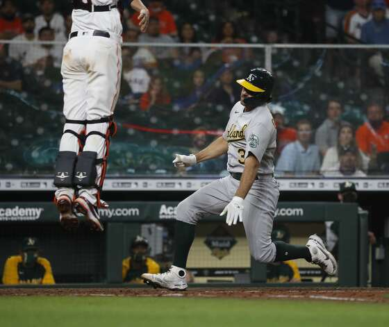 Oakland Athletics catcher Aramis Garcia (37) slides home as Houston Astros catcher Jason Castro (18) leaps up during the ninth inning of the Astros home opener MLB baseball game at Minute Maid Park, in Houston, Thursday, April 8, 2021. Astros beat the Oakland Athletics 6-2. Photo: Karen Warren/Staff Photographer / @2021 Houston Chronicle