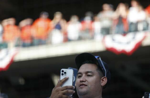 A fan takes photos during player introductions before the first inning of the Astros home opener MLB baseball game at Minute Maid Park, in Houston, Thursday, April 8, 2021. Photo: Karen Warren/Staff Photographer / @2021 Houston Chronicle