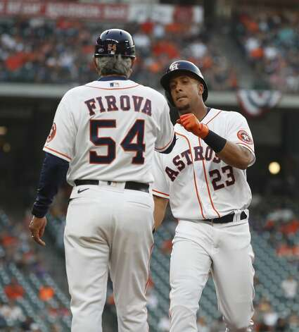 Houston Astros Michael Brantley (23) his single with first base coach Dan Firova (54) celebrates during the first inning of the Astros home opener MLB baseball game at Minute Maid Park, in Houston, Thursday, April 8, 2021. Photo: Karen Warren/Staff Photographer / @2021 Houston Chronicle