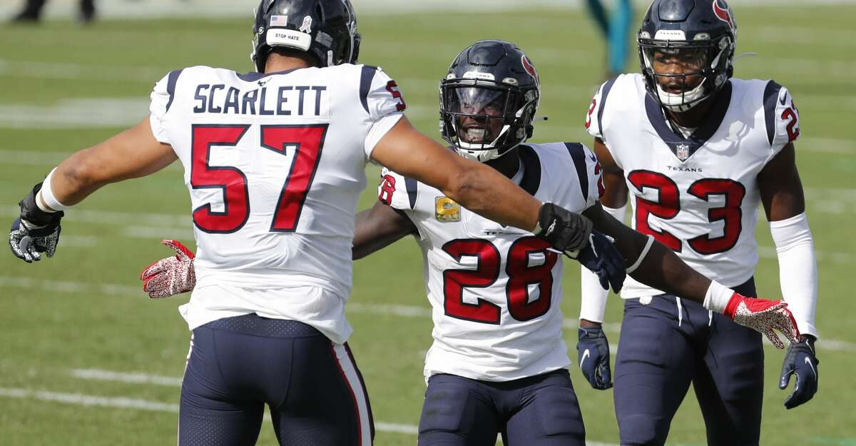 Houston Texans linebacker Brennan Scarlett (57), defensive back Michael Thomas (28) and cornerback Phillip Gaines (29) celebrate stopping Jacksonville Jaguars running back Chris Thompson during the first half of an NFL football game at TIAA Bank Field Sunday, Nov. 8, 2020, in Jacksonville.