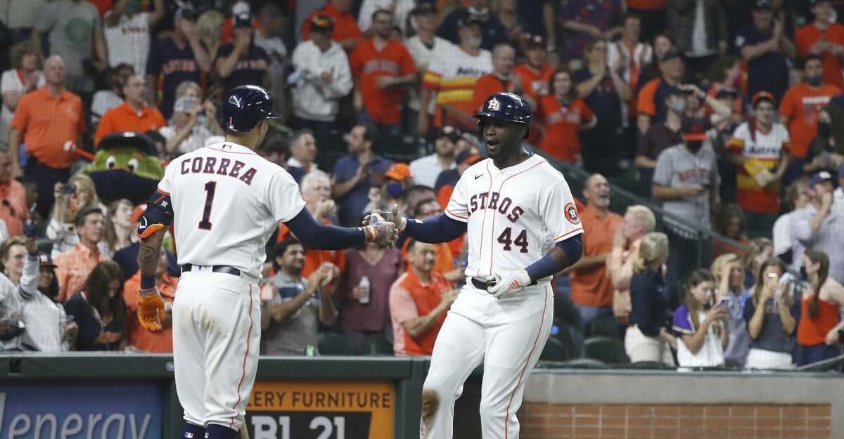 Houston Astros Yordan Alvarez (44) reacts with Carlos Correa (1) after his home run during the sixth inning of the Astros home opener MLB baseball game at Minute Maid Park, in Houston, Thursday, April 8, 2021.