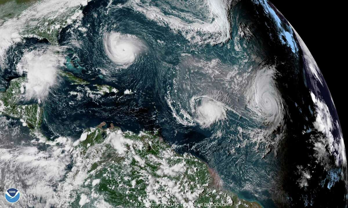This enhanced satellite image made available by NOAA shows Tropical Storm Florence, upper left, in the Atlantic Ocean on Tuesday, Sept. 11, 2018 at 3:30 p.m. EDT. At center is Tropical Storm Isaac and at right is Hurricane Helene.
