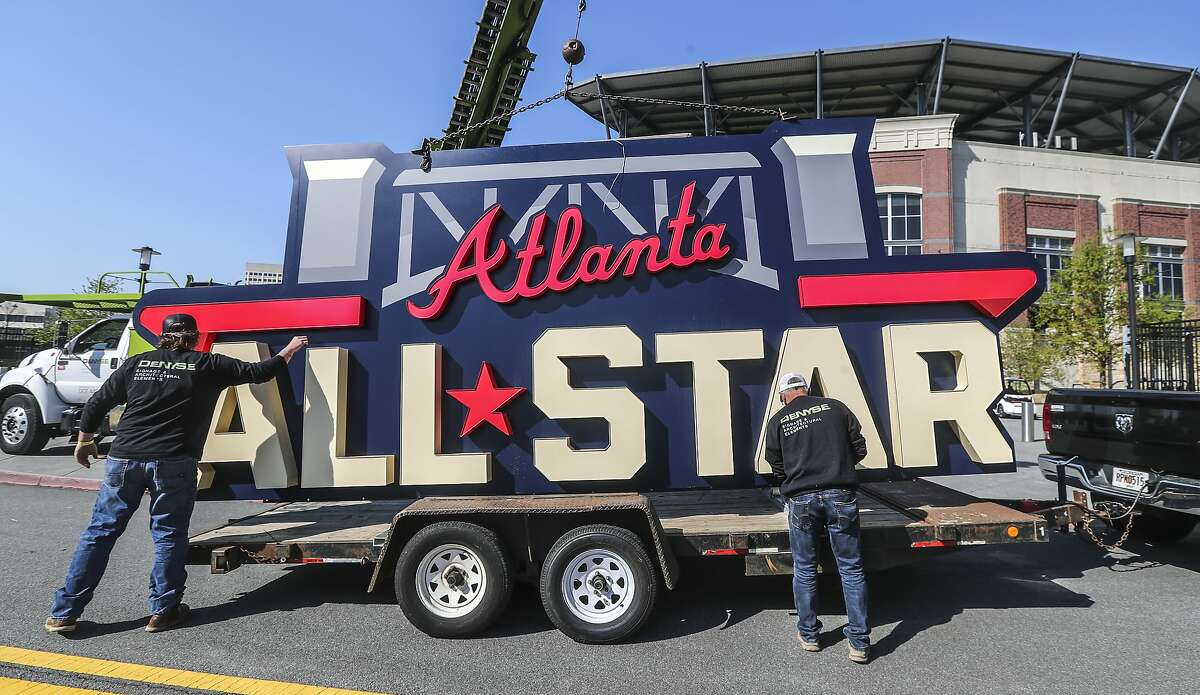 Workers load an All-Star Game sign onto a trailer after it was removed from Truist Park near Atlanta on Tuesday. Major League Baseball plans to relocate the game to Coors Field in Denver over objections to sweeping changes to Georgia's voting laws.