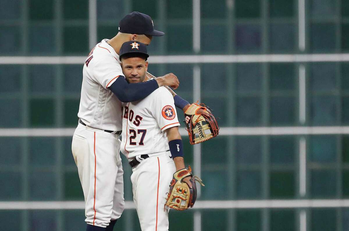 Houston Astros second baseman Jose Altuve (27) hugs shortstop Carlos Correa (1) after the Astros 6-2 win over the Oakland Athletics in the Astros home opener MLB baseball game at Minute Maid Park, in Houston, Thursday, April 8, 2021.