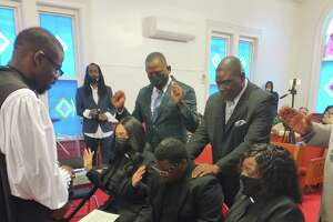 Apostle Robert Smith of Virginia lays his hands on Michael Walker as he, along with Chamar Logan and Aurelia Franklin, are officially installed as ministers at the annual Holy Gathering celebration on March 28 in Middletown.