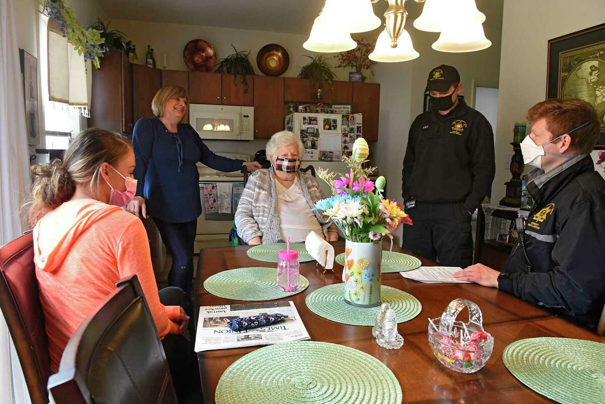 EMT's and Paramedics James Mudge, second from right, and David Gallati, right, talk to Mary Nardiello after administering a COVID-19 vaccine for her in her home on Friday, April 2, 2021 in Albany, N.Y. Nardiello's daughter Pat Mangini, second from left, stands behind her while Mary's aid Cait Amodeo sits at the table. (Lori Van Buren/Times Union)