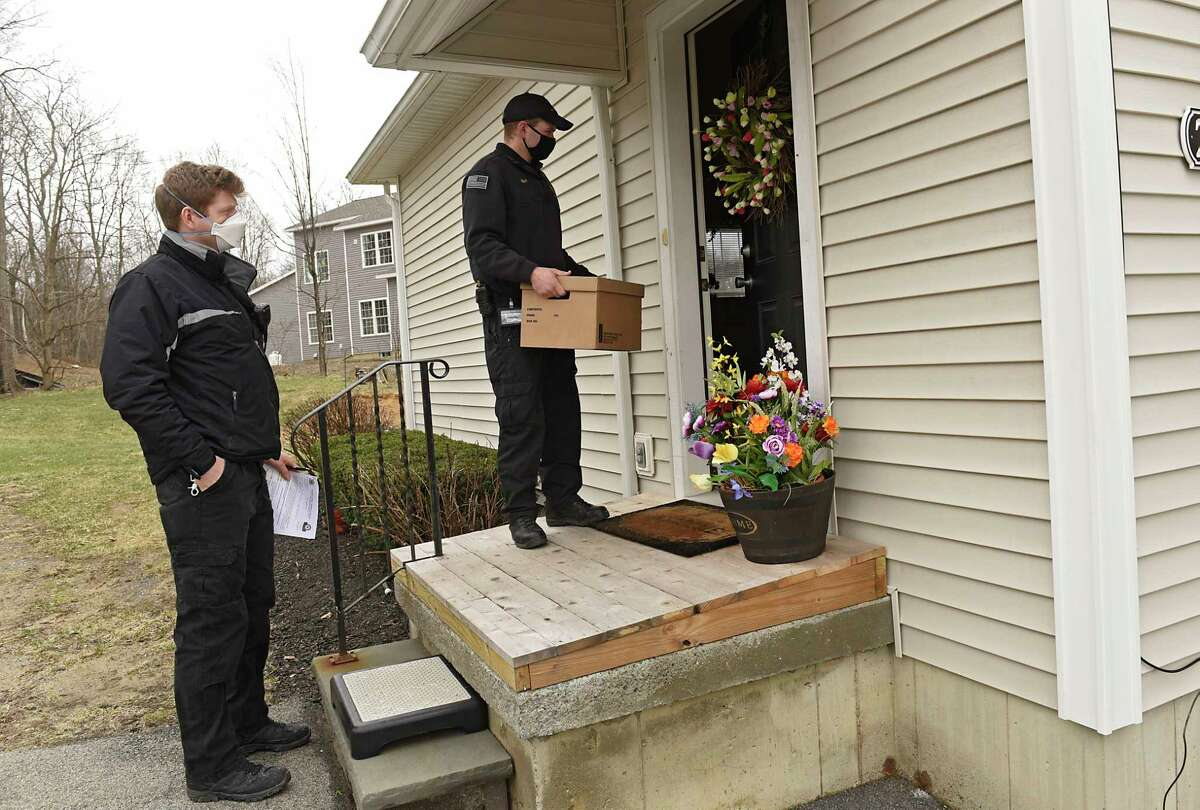 EMT's and Paramedics David Gallati, left, and James Mudge arrive at Mary Nardiello's home to administer her COVID-19 vaccine for her on Friday, April 2, 2021 in Albany, N.Y. Gallati and Mudge work in the EMS division of the Albany County Sheriff's Department. (Lori Van Buren/Times Union)