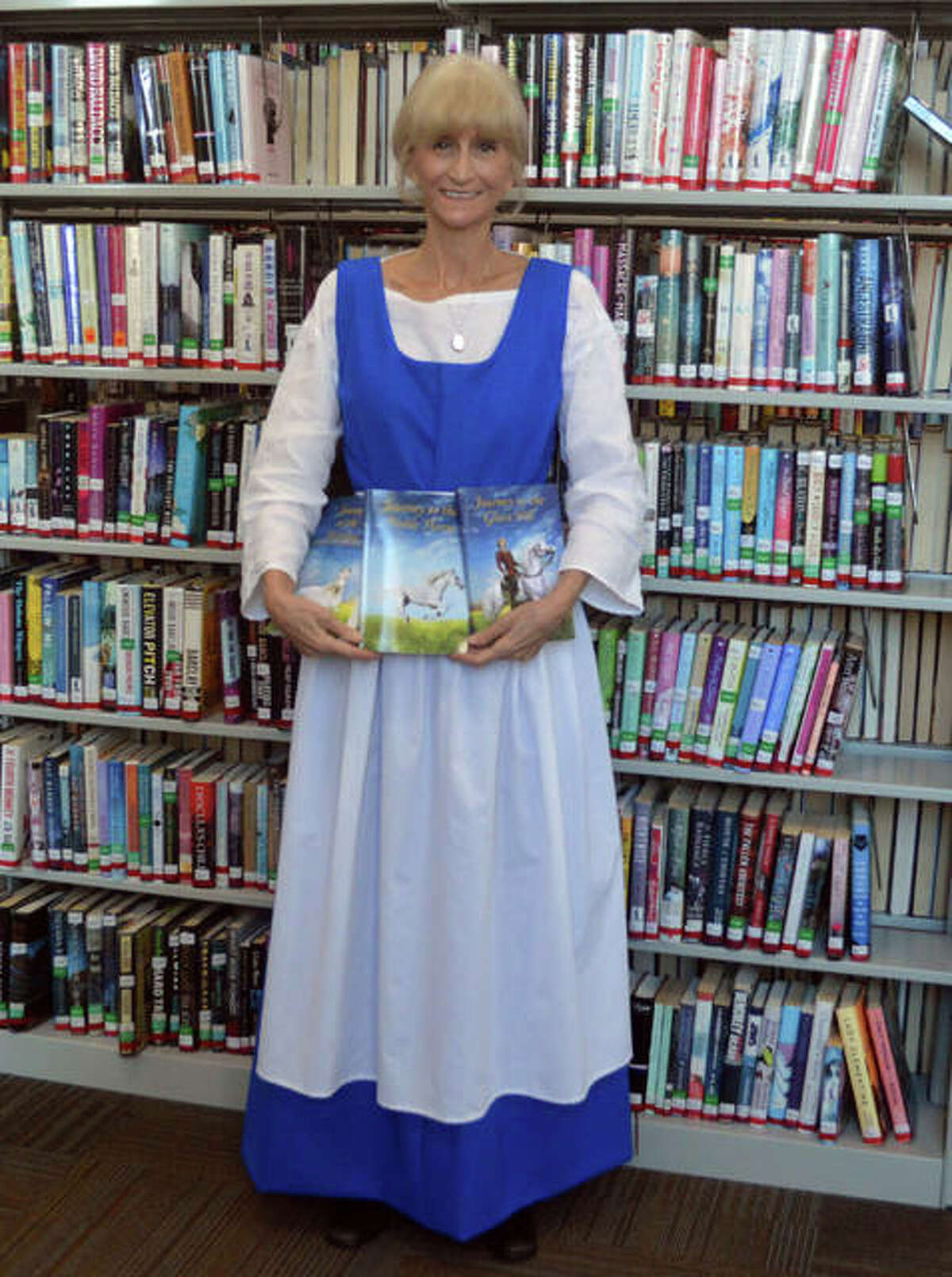 Diane Frazier, a retired kindergarten teacher from Glen Carbon, recently completed the Journey Books of Faith and Family trilogy, which are targeted at middle-grade students. She is wearing a 1600s period costume that she hopes to wear to schools to talk about the books.