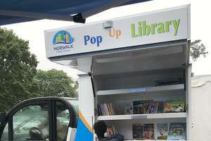 A Norwalk resident peruses the books on the Norwalk Library's Pop-Up Truck. The truck has been visiting food sites at local schools and community centers, handing out free books and DIY craft bags this summer.