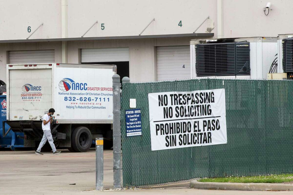 A driver walks past his truck after pulling into the National Association of Christian Churches facility, where hundreds of migrant teenaged girls are being housed Monday, April 5, 2021 in Houston.