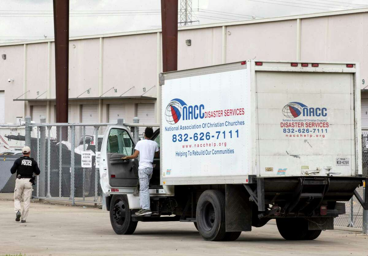 A U.S. Department of Homeland Security officer checks on a truck driver outside the National Association of Christian Churches facility, before allowing access to the facility where hundreds of migrant teenaged girls are being housed Monday, April 5, 2021 in Houston.