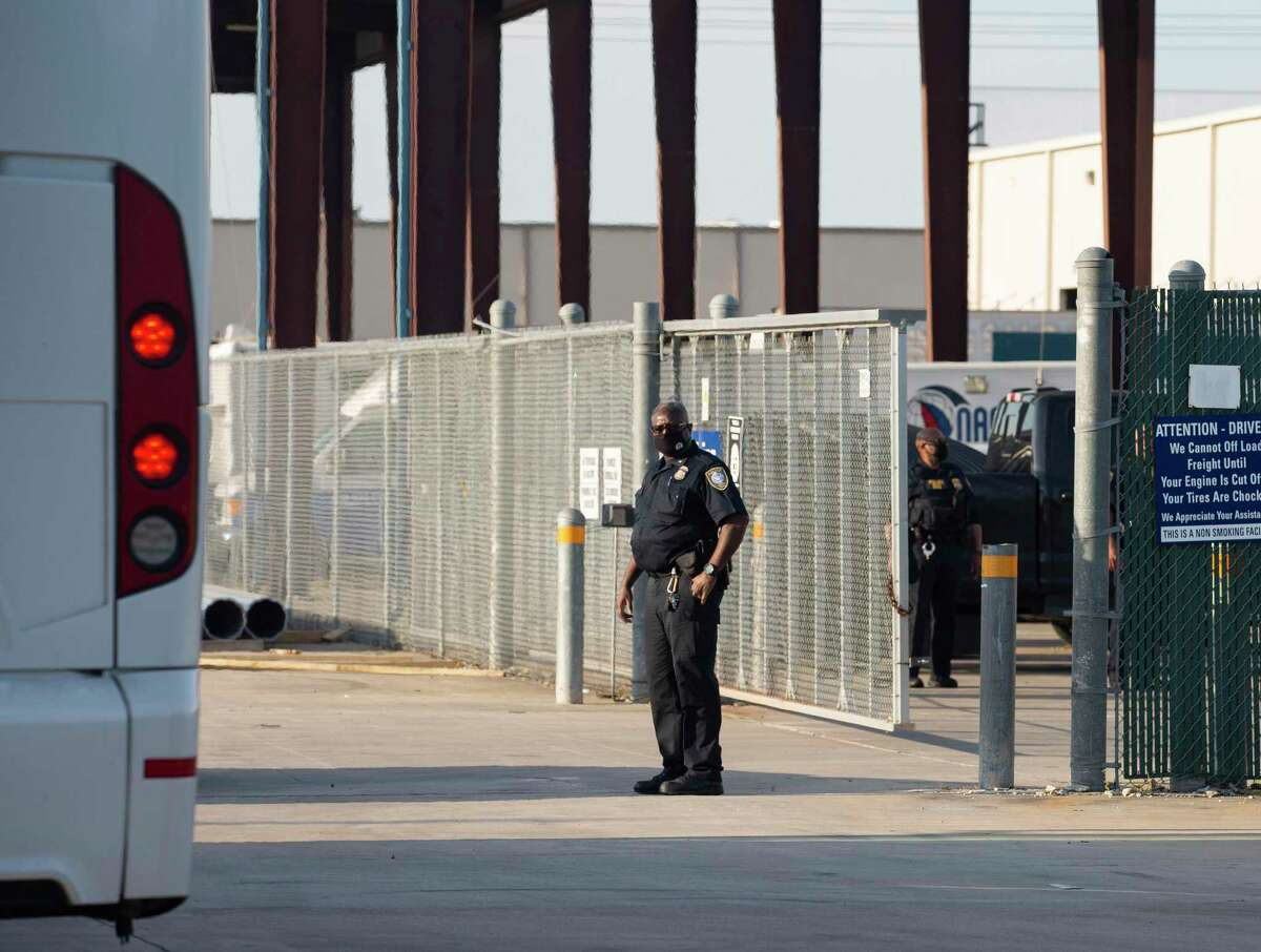 Federal Protective Service police opening the entrance of a holding facility to allow the first bus carrying migrant girls from the border pulling up Friday, April 2, 2021, in Houston.