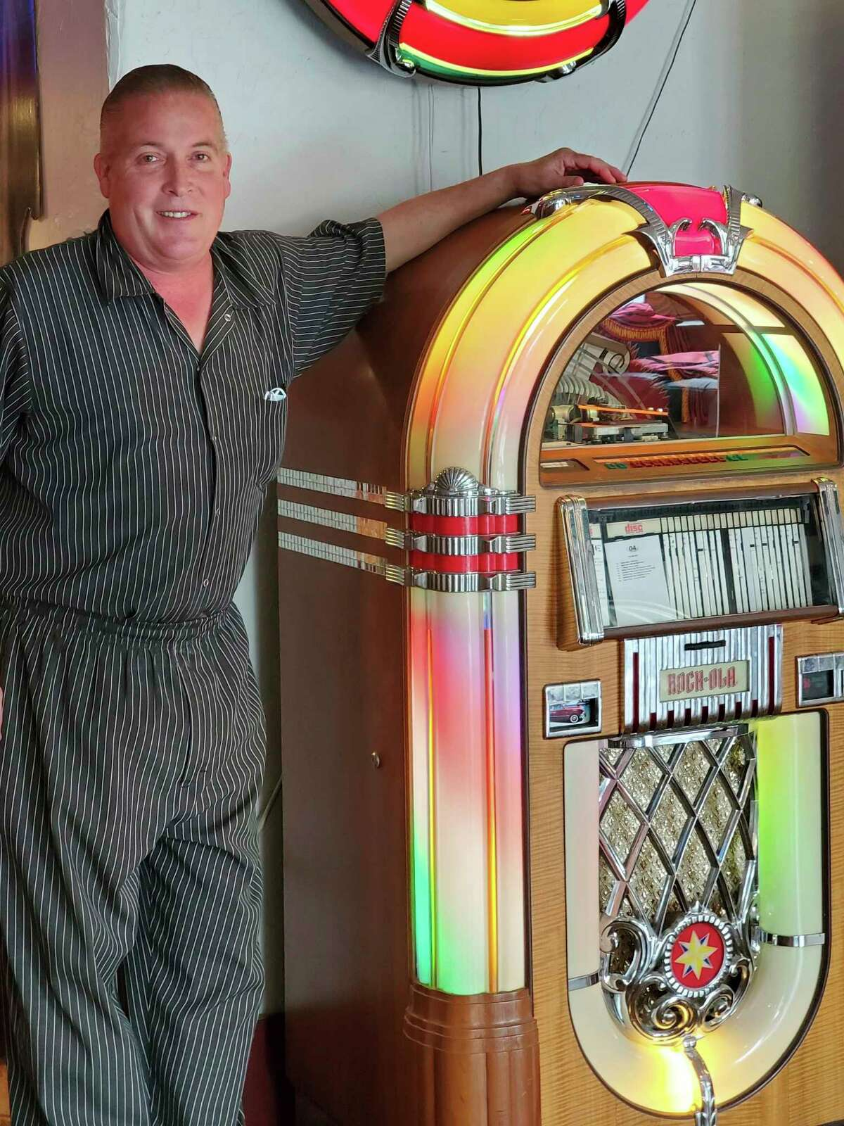Kevin Wiley, who co-owns The Pasta House with his wife Helen, poses for a photo next to a classic jukebox in his restaurant. (Scott Nunn/Huron Daily Tribune)