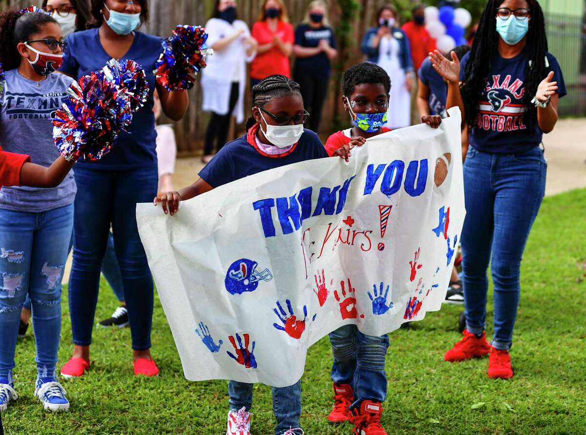 Children at the Mission of Yahweh hold up a home-made thank you sign for the McNair family and the Houston Texans for providing them playground equipment to enjoy.