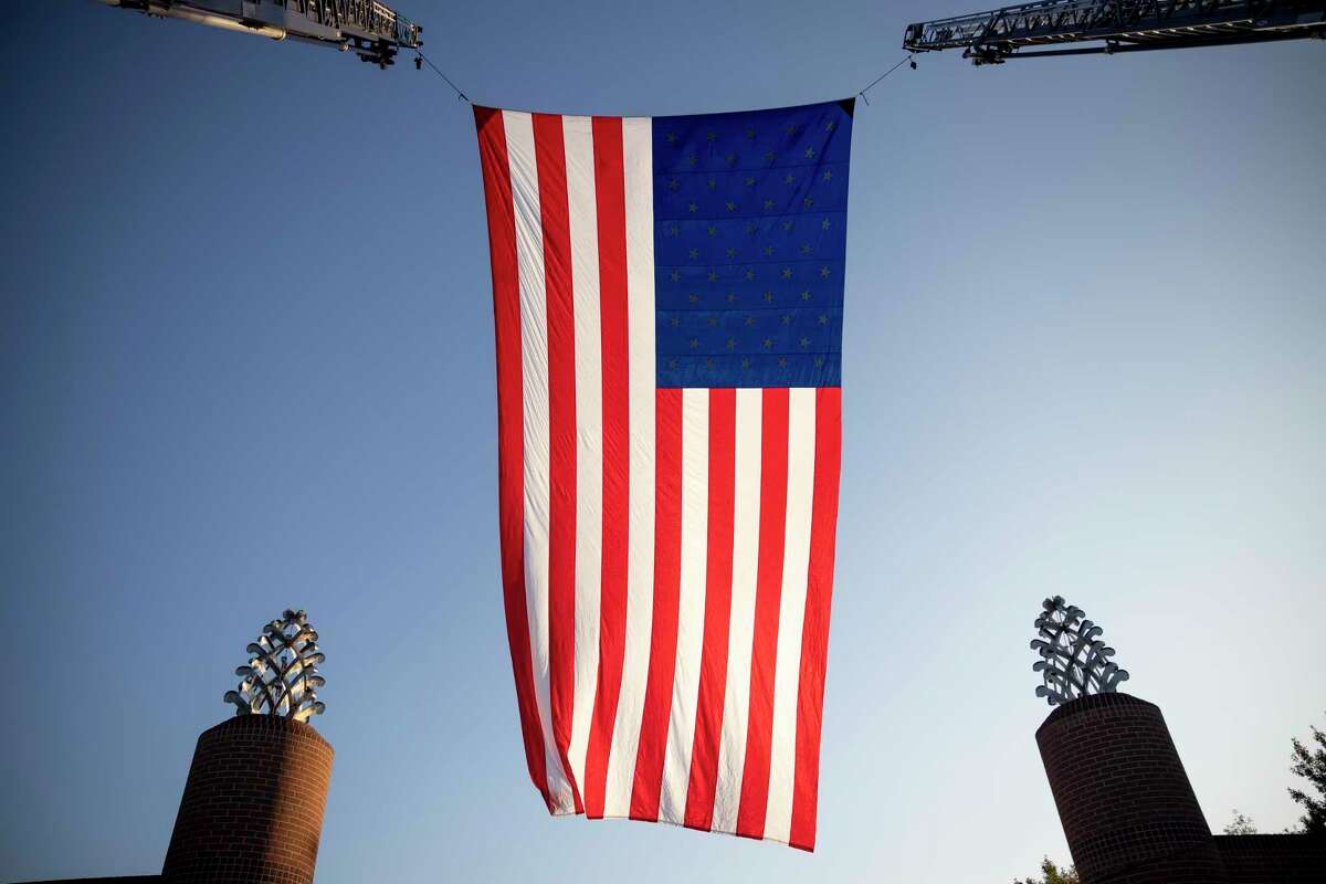 The United States flag is flown during the annual Veterans Day Tribute and Celebration in Town Green Park, Wednesday, Nov. 11, 2020, in The Woodlands. Social distancing was enforced and face masks or coverings were highly recommended during the ceremony.
