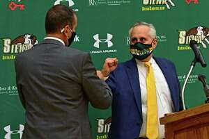 Jim Jabir, new Siena women's basketball head coach, left, gets a COVID-19 fist bump from John D'Argenio, Siena College director of athletics, as he is introduced at a press conference on Thursday, April 8, 2021 in Loudonville, N.Y. Jabir coached Siena from 1987 to 1990. (Lori Van Buren/Times Union)