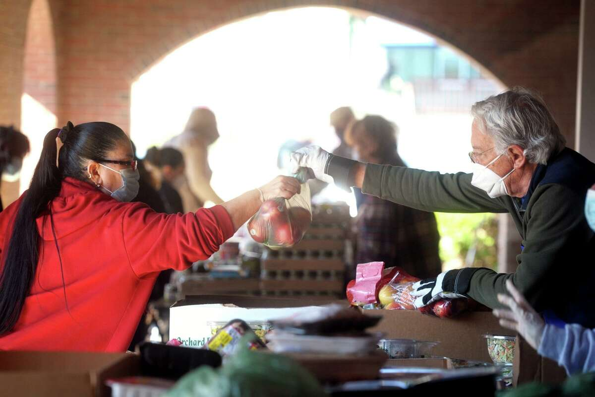 Volunteer Tony Montemurno, of Stratford, hands a woman a bag of apples as she and others pick up groceries at the weekly food pantry event outside Bridgeport Rescue Mission's new Community Care Clinic, currently under construction in Bridgeport, Conn. April 8, 2021.