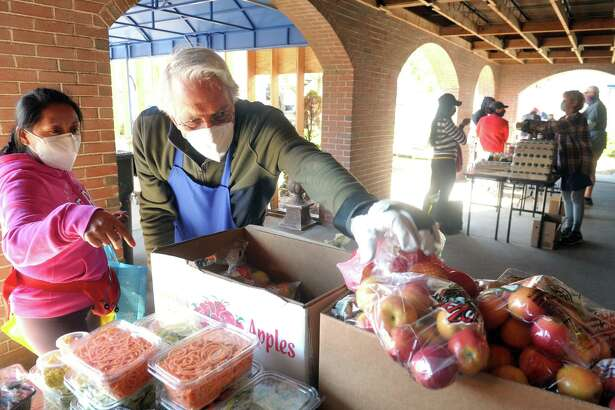 Volunteer Tony Montemurno, of Stratford, reaches for a bag of apples as he assists a woman picking up groceries at the weekly food pantry event outside Bridgeport Rescue Mission's new Community Care Clinic, currently under construction in Bridgeport, Conn. April 8, 2021.