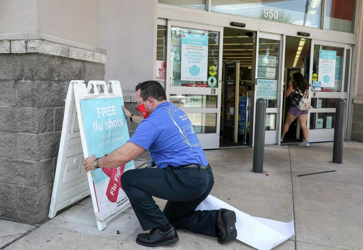 John Kalvaitis, store manager, puts up a sign advertising flu shots Thursday, Aug. 13, 2020, at a Walgreens location in Houston.