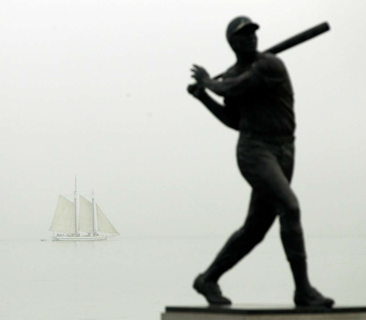 A boat passes behind the statue of Willie McCovey outside of the stadium before Game 3 of baseball's National League Championship Series between the Philadelphia Phillies and the San Francisco Giants, Tuesday, Oct. 19, 2010, in San Francisco. (AP Photo/Marcio Jose Sanchez)
