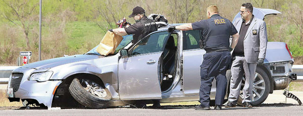 Police gather evidence from a badly damaged Chrysler 300 Friday after it crashed in a work zone at the Cahokia Diversion Canal bridge on southbound Illinois 255. The vehicle fled a traffic stop around noon pursued by law enforcement authorities from Roxana, South Roxana, Hartford, Wood River and Bethalto. Two people were taken into custody and two people were treated at the scene for injuries. The crash backed up traffic on southbound Illinois 255 for more than a mile.