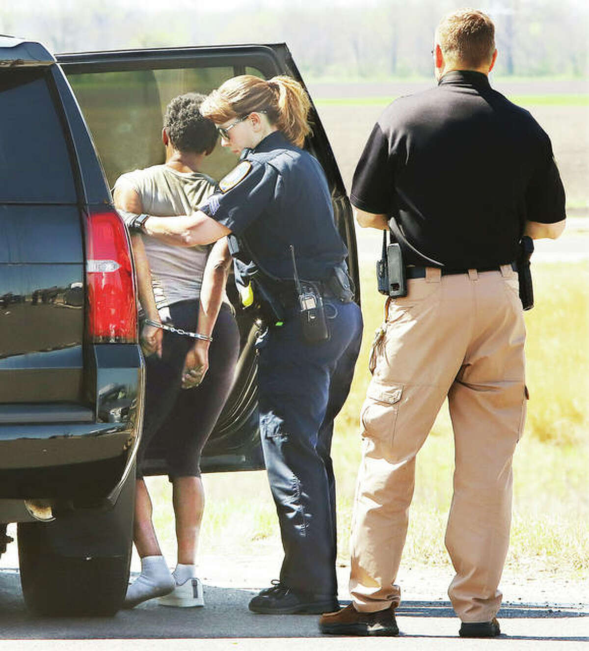 Roxana Police Chief Will Cunningham, right, supervises as a female Bethalto Police officer called to the scene to assist searches a female suspect Friday.