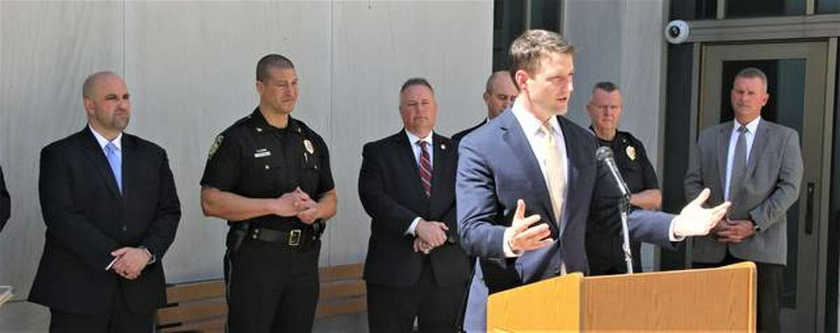 """Madison County State's Attorney Thomas Haine, flanked by county and federal law enforcement officials, while talking about the results of a meeting between Madison County, state and federal law enforcement officials concerning """"cross-river"""" crime."""