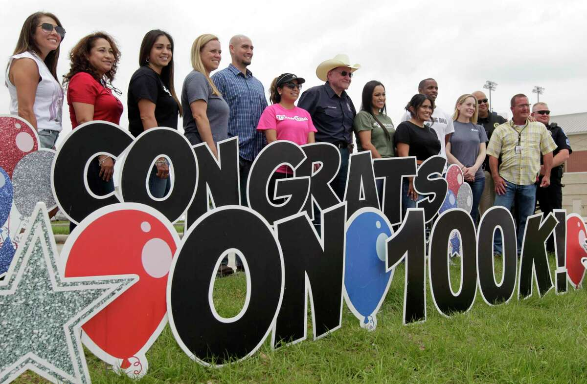 Medical personnel and Montgomery County officials pose for a photo as they celebrate reaching 100,000 coronavirus vaccines at the county's mass vaccination site at Woodforest Bank Stadium, Friday, April 9, 2021, in Shenandoah.