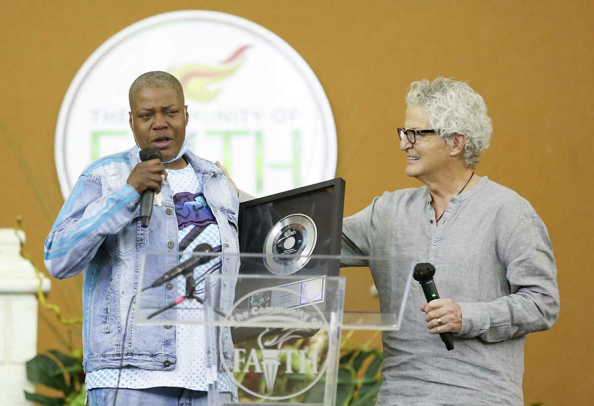 """Kevin Cronin, lead singer of REO Speedwagon, gives LaTonya Floyd, sister of George Floyd, a platinum album of the band's """"Keep on Loving You"""" song at The Community of Faith Church in Houston for a prayer vigil for the family on Friday, April 9, 2021. Cronin read in People Magazine about the last time George and LaTonya talked on the phone and how they sang that song to each other. It was a song they had been sharing together over the years."""