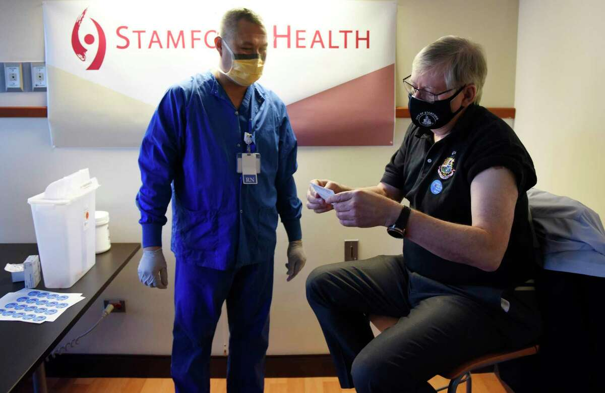 Stamford Mayor David Martin looks over his vaccination card with Cecil Chan, RN, after receiving the first dose of the COVID-19 vaccine at Stamford Hospital in Stamford, Conn. Monday, March 8, 2021.