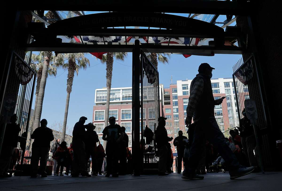 Fans enter the ballpark from Willie Mays Plaza before the San Francisco Giants played the Colorado Rockies at Oracle Park in San Francisco Calif., on Friday, April 9, 2021. After a year confined to watching baseball at home, fans were eager to see a game in-person.