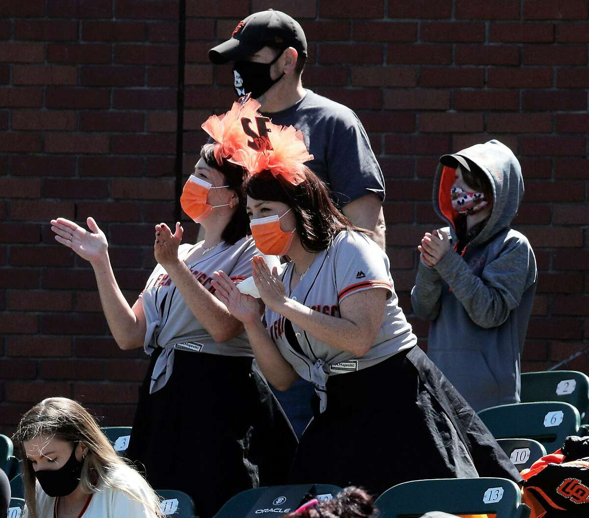 Fans cheer during introductions before the Giants played the Rockies at Oracle Park. Fans did all the things that their cardboard selves couldn't - holler, take selfies and buy caps with holograms on them.