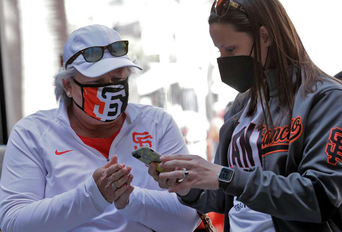 Morgan Matthews, right, helps her mom, Kim Peters, both from Fresno, navigate the new entrance apps on her phone as fans enter the ballpark before the San Francisco Giants played the Colorado Rockies at Oracle Park in San Francisco Calif., on Friday, April 9, 2021.